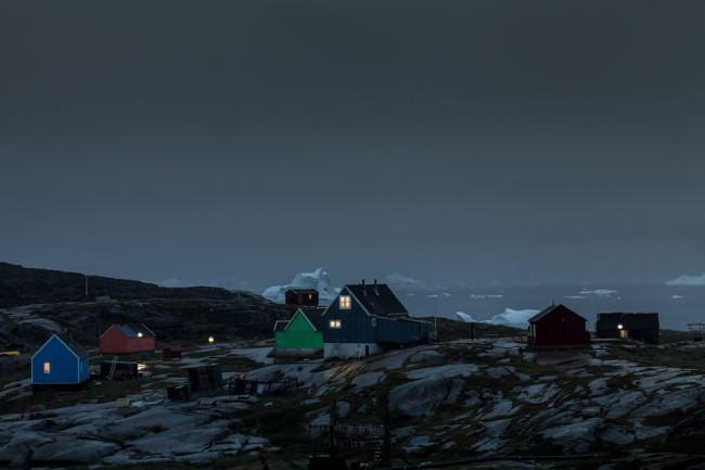 Ein Dorf bei Nacht mit erleuchteten Fenstern.