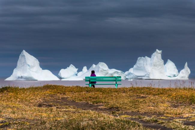 Ein Mensch auf einer grünen Bank betrachtet die Eisberge auf dem Meer.