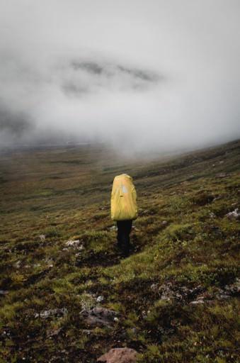 Eine Person mit großem gelben Rucksack auf einer nebligen Wiese.