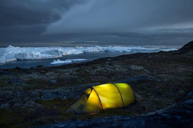 Ein gelbes hell erleuchtetes Zelt vor einem dunklen Eismeer.