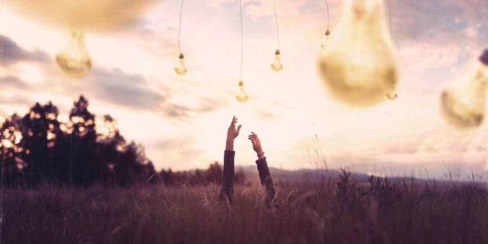 Hände greifen nach riesigen Glühbirnen die vom Himmel hängen.