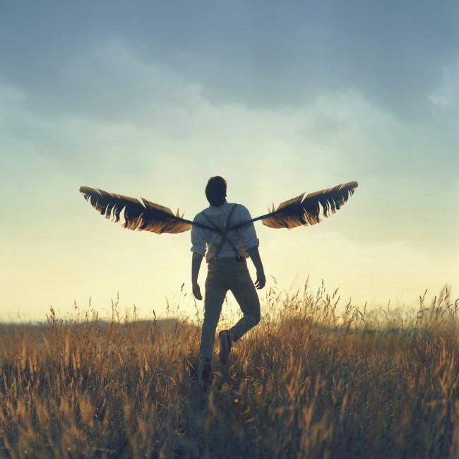 Mann mit großen Federn als Flügel.
