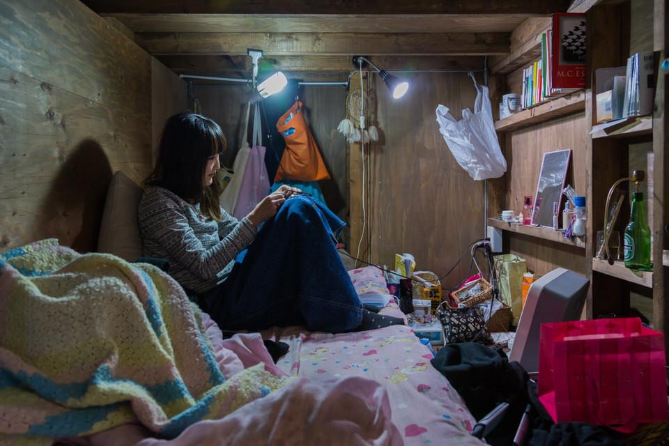 Eine Frau sitzt auf einem Bett eines winzigen Raumes.