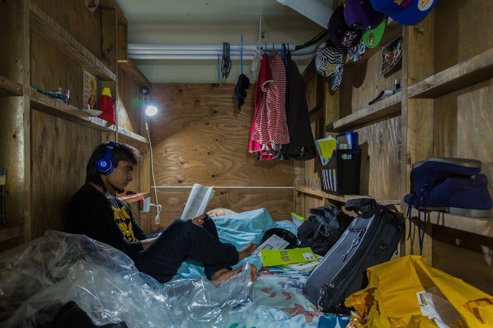 Ein mann mit Kopfhörern liest auf einem Bett.