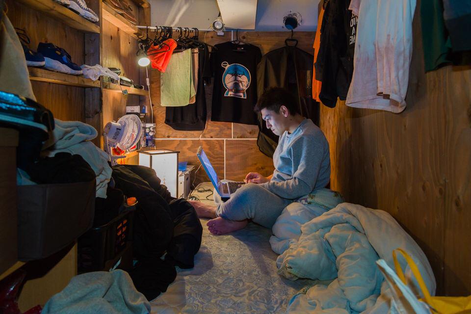 Ein mann mit Laptop auf einem Bett.