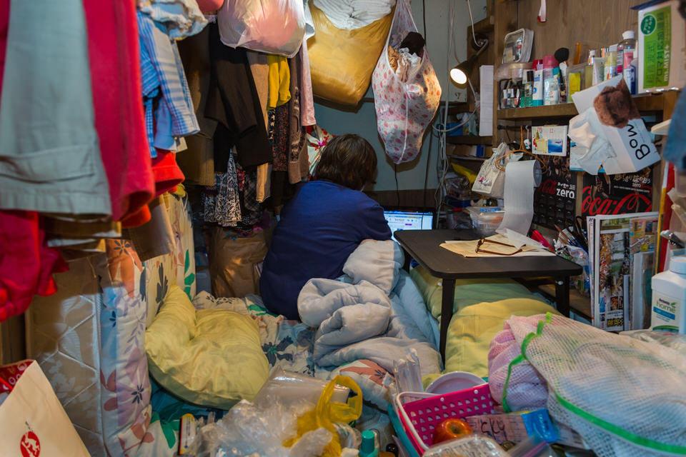 Eine Person in einem winzigen Zimmer voller Gegenstände.