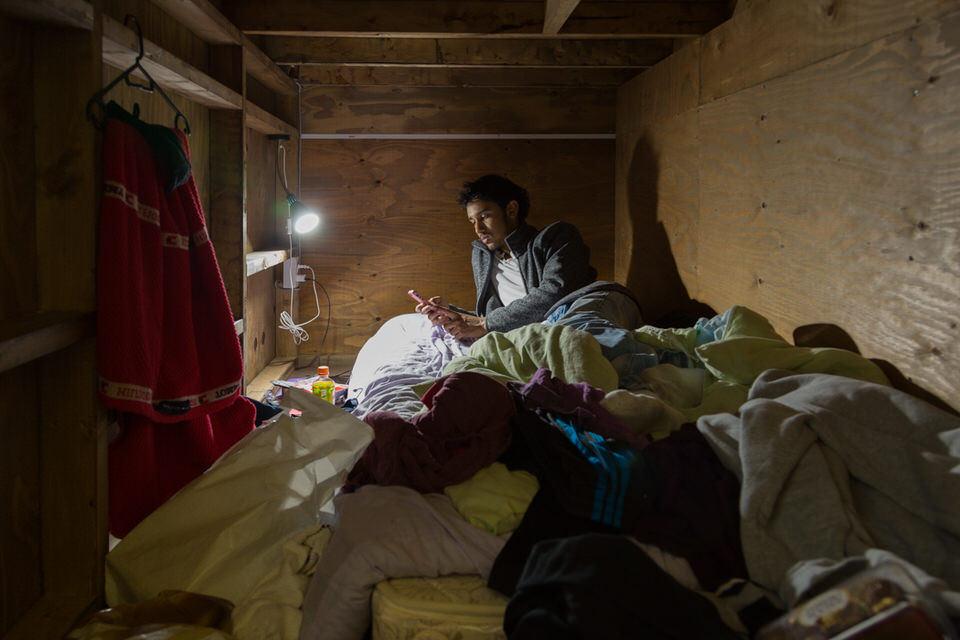 Ein Mann mit Handy auf seinem Bett liegend.