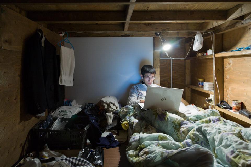 Ein Mann mit Laptop im Bett.