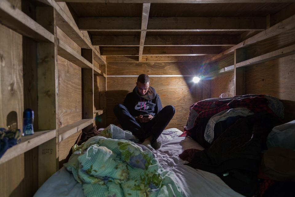 Ein Mann in einem winzigen Holzzimmer.