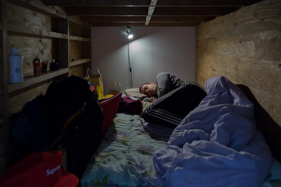 Ein Mann schläft in einem winzigen Zimmer.