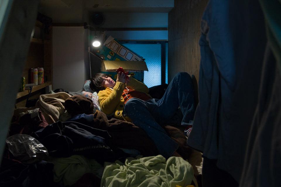 Eine Person mit Handy liegt auf einem Bett in einem vollgestellten Zimmer.