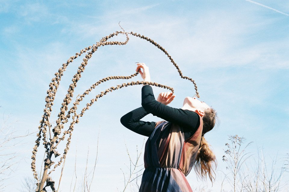 Mädchen mit trockener Pflanze vor blauem Himmel.