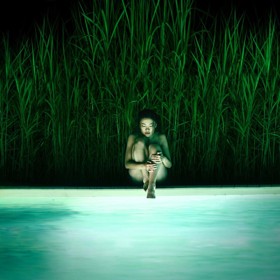 Nackte Frau sitzt mit angewinkelten Beinen am Rand eines beleuchteten Pools in der Dunkelheit, hinter ihr hohes grünes Gras.