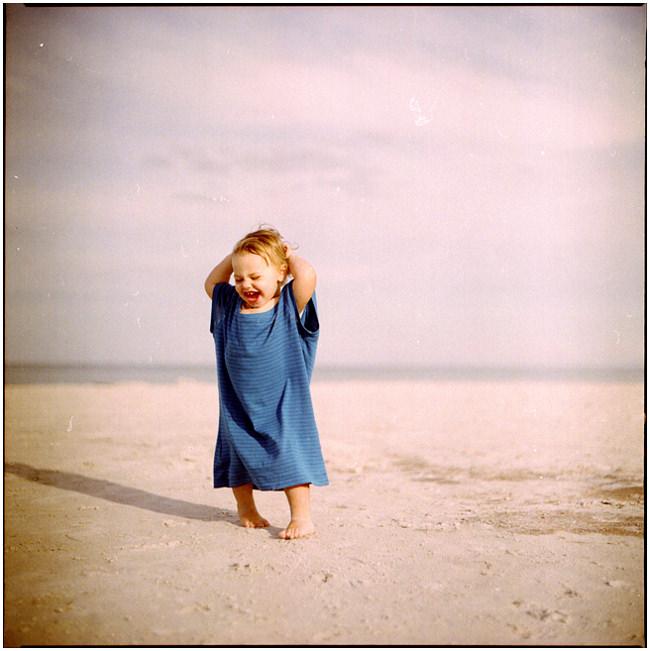 Ein kleines Mädchen in einem blauen Hemdchen steht jauchzend am Strand.