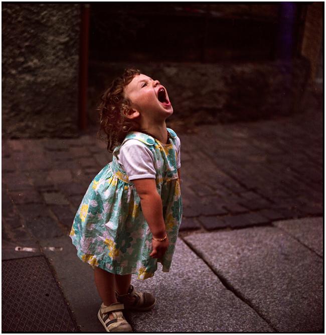 Ein kleines Mädchen im Kleid steht auf der Straße und schreit.