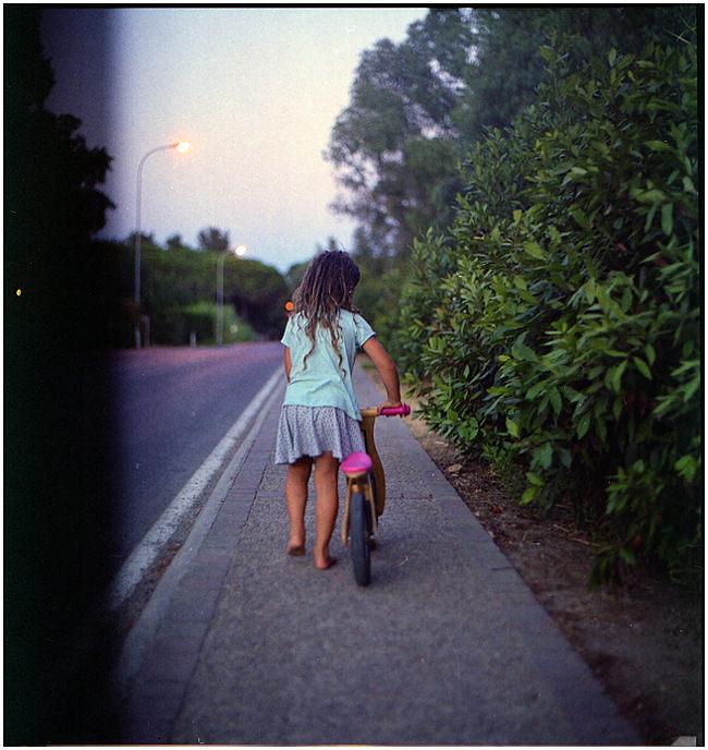 Ein Mädchen schiebt ein Fahrrädchen den Bürgersteig entlang.