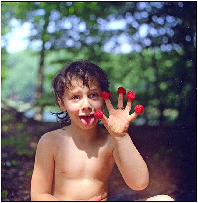 Ein Mädchen hat Himbeeren auf den Fingerspitzen aufgesteckt.