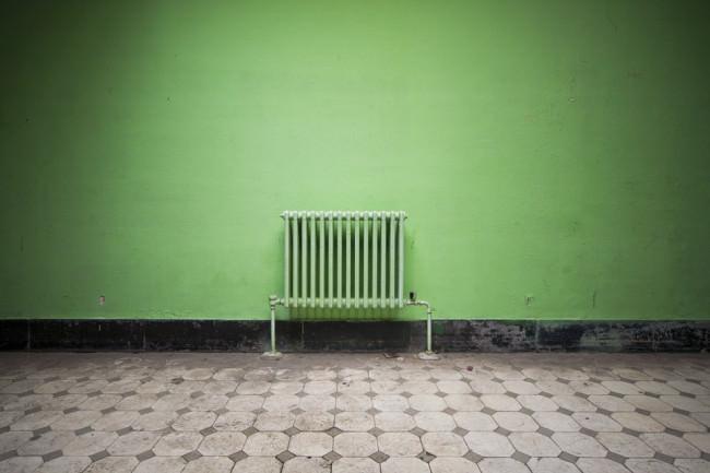 Heizung vor grüner Wand.