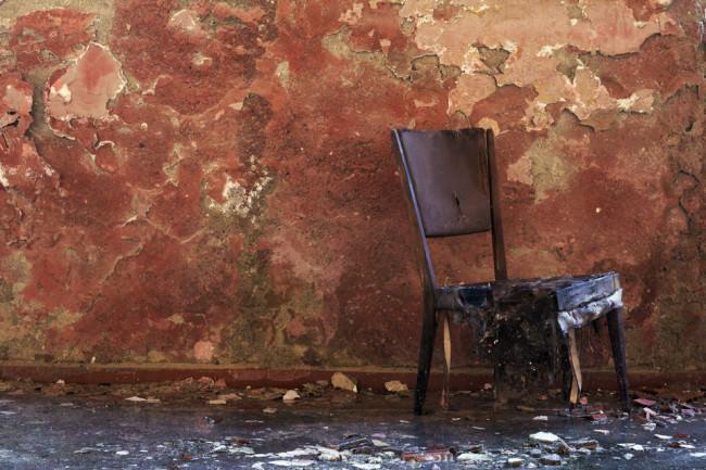 Ein alter Stul vor einer roten Wand.
