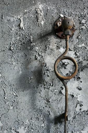 Ein verrosteter Eisenring an einer abbläternden Tapete.