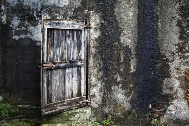 Eine alte Holztür an einer Mauer.
