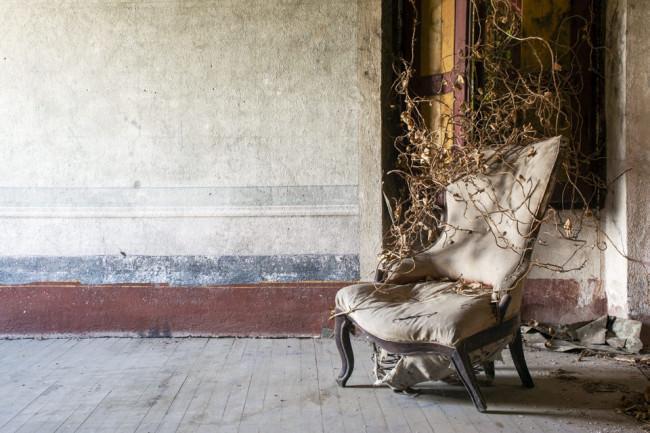 Ein alter STul mit Gestrüpp in einem verlassenen Zimmer.
