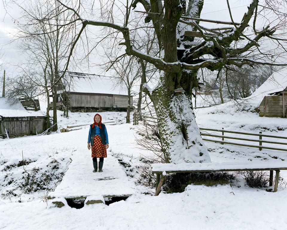 Eine alte Frau steht im Schnee in einem Dorf in den Karpaten.