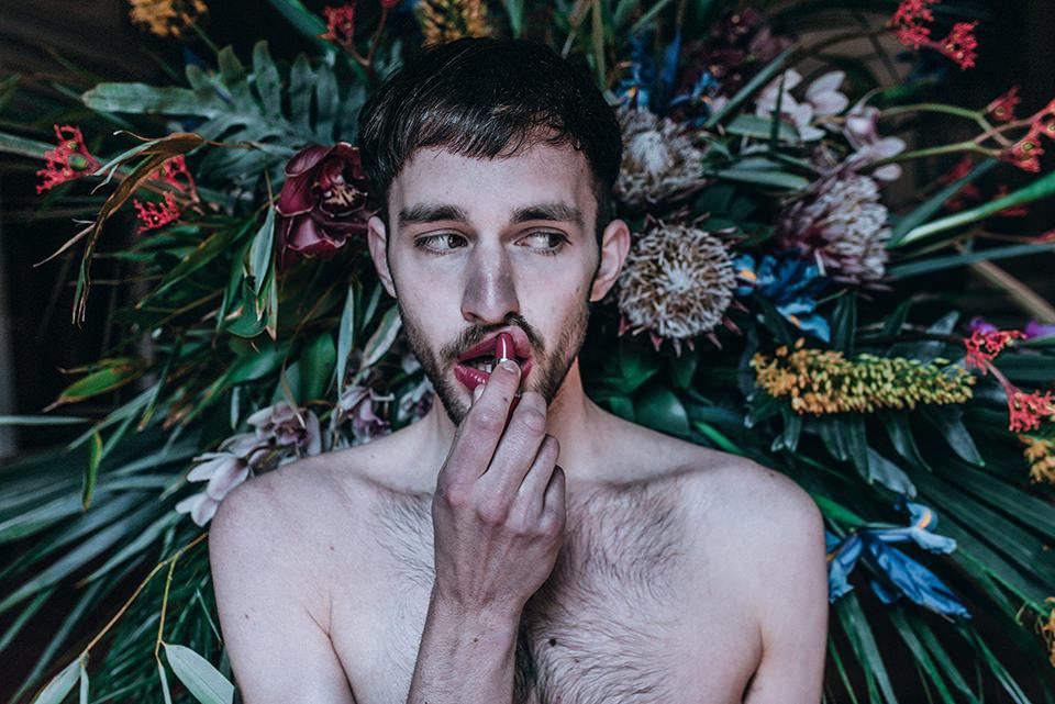 Ein Mann mit Lippenstift vor einem Blumenstrauß