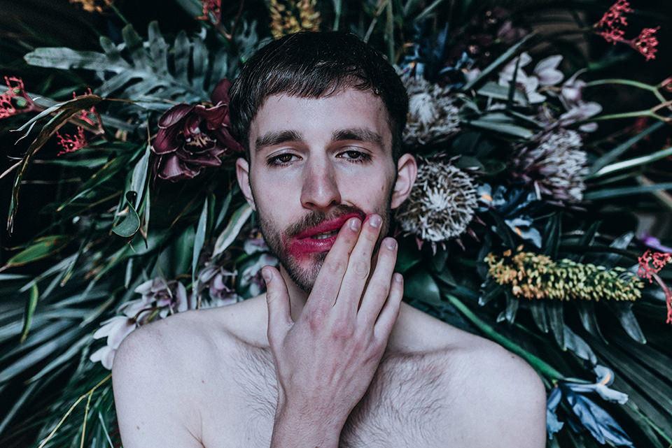 Ein Mann mit rotverschmierten Lippen vor einem Blumenstrauß.