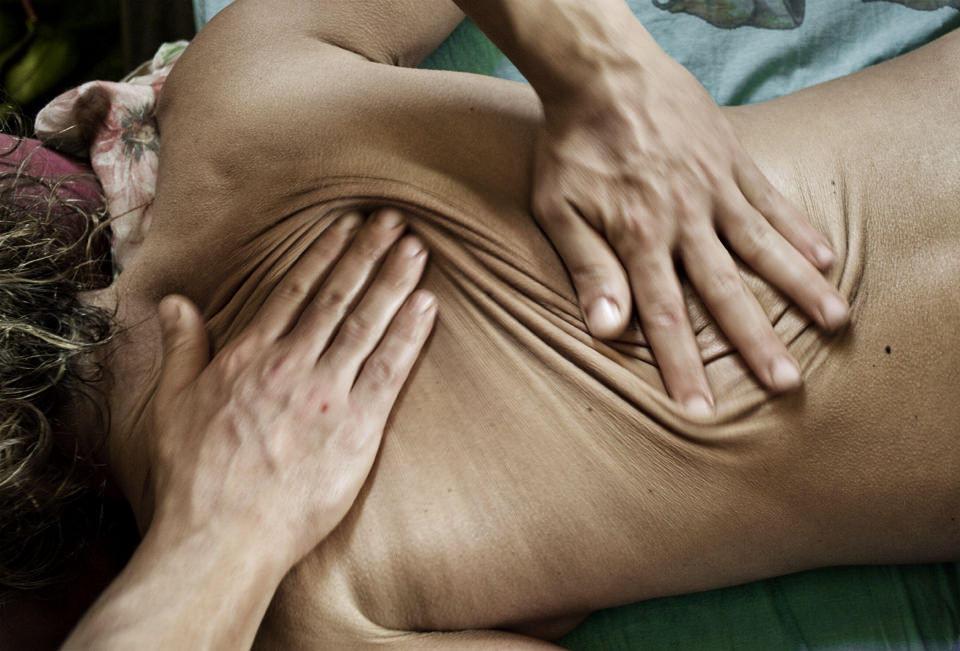 Zwei Hände liegen auf einem Rücken
