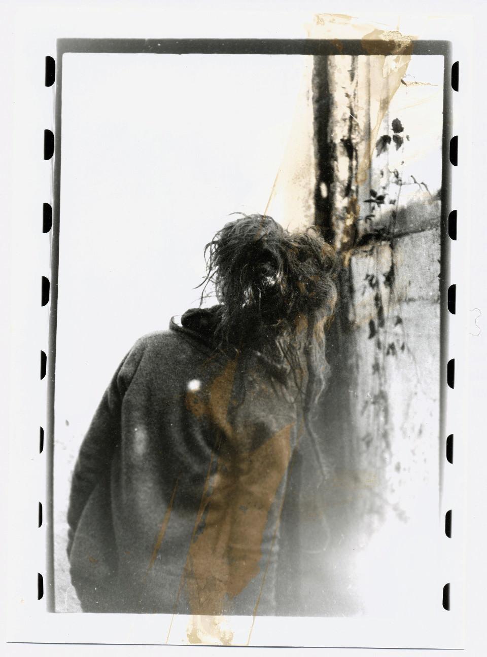 Mädchen steht mit dem Rücken zur Kamera neben einem Fenster.