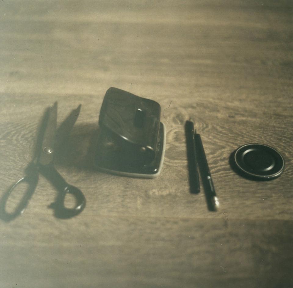 Eine Schere, ein Locher, Stifte und ein Kamerdeckel.