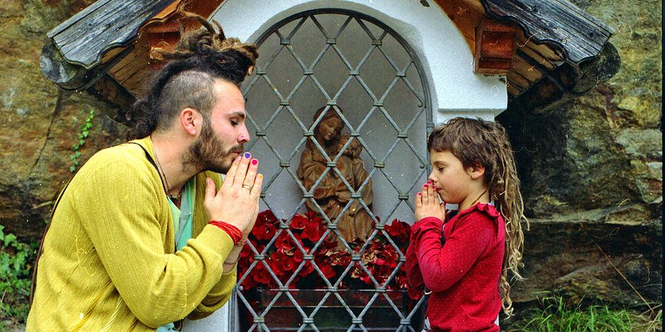 Ein Mann und ein Mädchen beten vor einem bunten Altar.