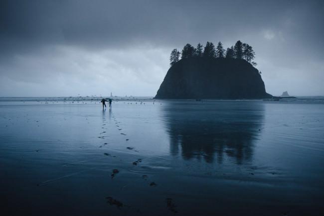Zwei Menschen laufen im Watt.