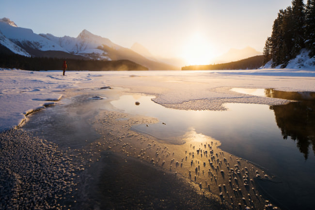 Gegenlicht an einem offenen See mit verschneitem Gebirge im Hintergrund.