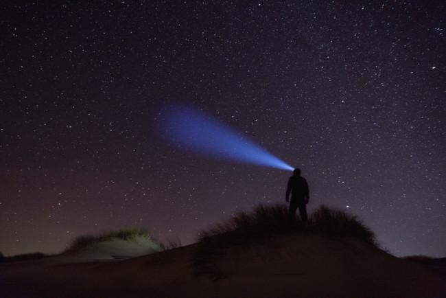 Eine Person schaut mit einer Stirnlampe in den Sternenhimmel.