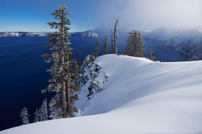Schneebedckter Wald mit Ausblick auf einen Kratersee.