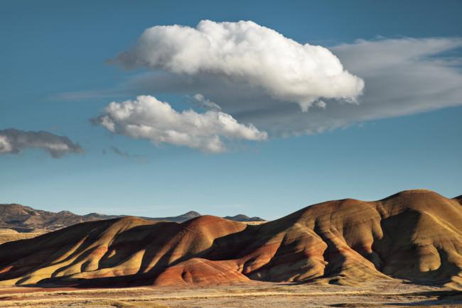 Wüstenlandschaft mit strahlend blauem Himmel und Wolken über Hügeln.
