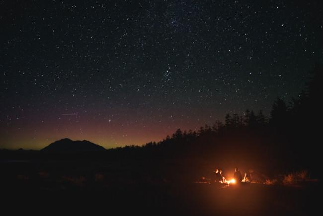 Langerfeuer mit Menschen unter Sternenhimmel.