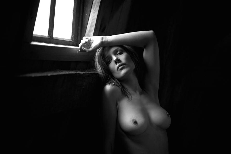 Aktbild einer Frau vor einem Fenster