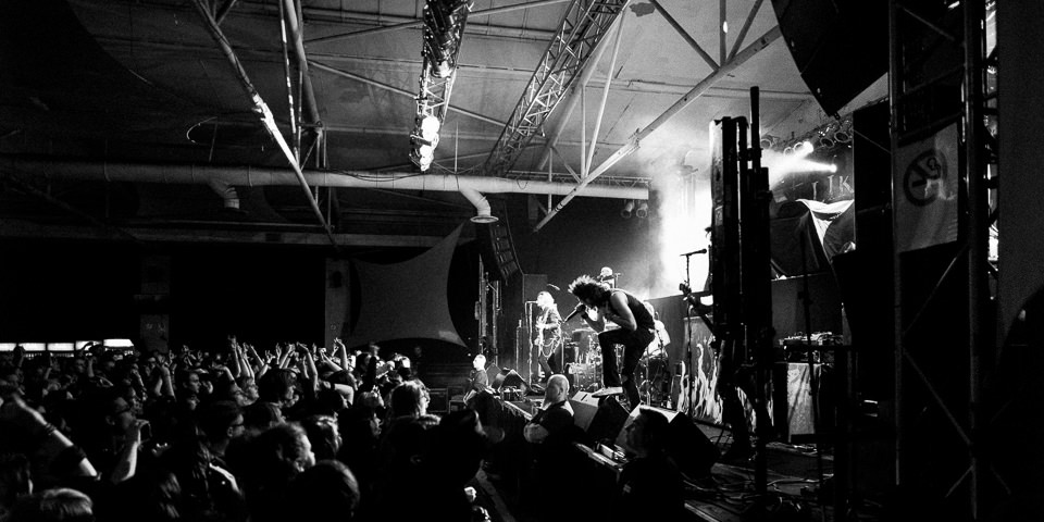 Ein Sänger steht vor einer Menge Fans und singt ins Mikrofon.