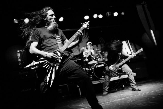 Konzertfotografie: Eine Metalband von vorne, die Haaren fliegen.