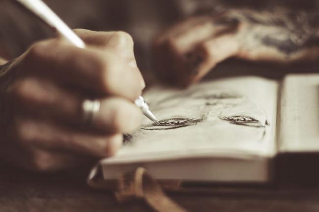 Hände zeichnen ein Gesicht.