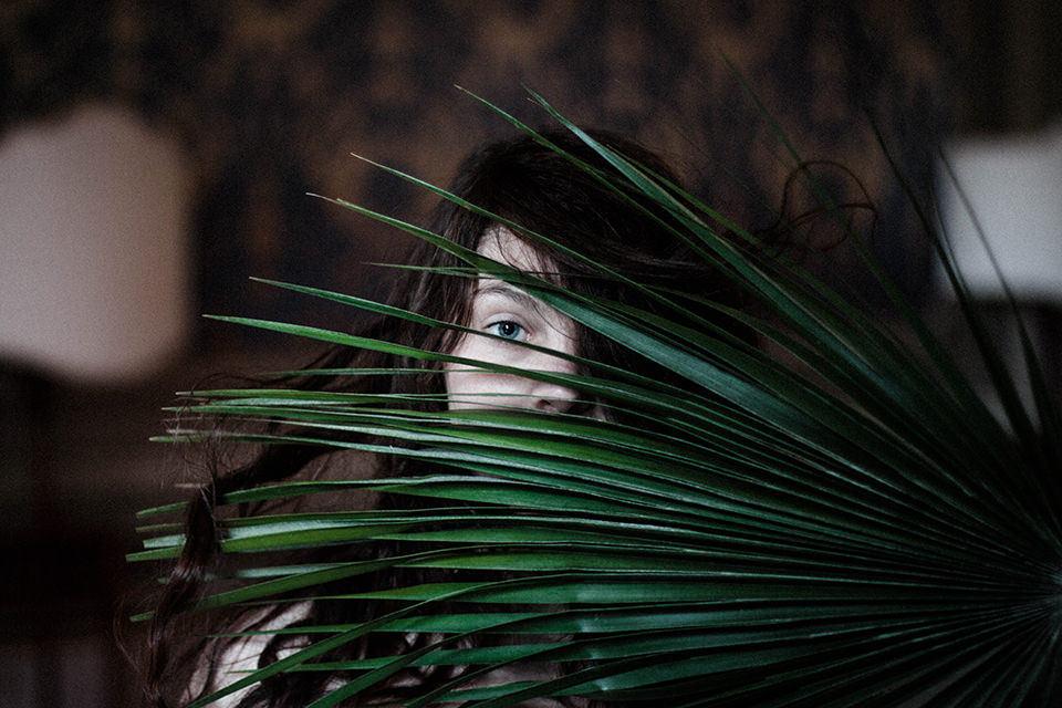 Eine Frau hinter einem Farnblatt.