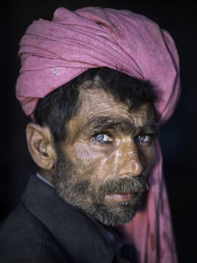 Ein Mann mit tiefblauen Augen und rosarotem Turban schaut in die Kamera.