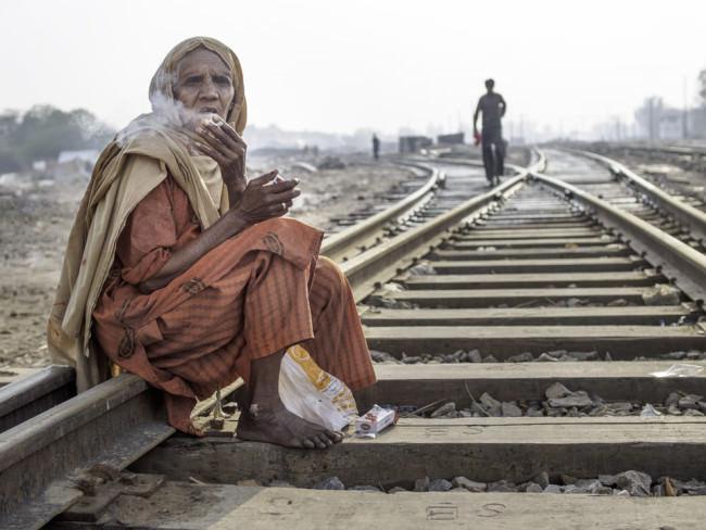 Eine rauchende Frau sitzt auf Bahngleisen.