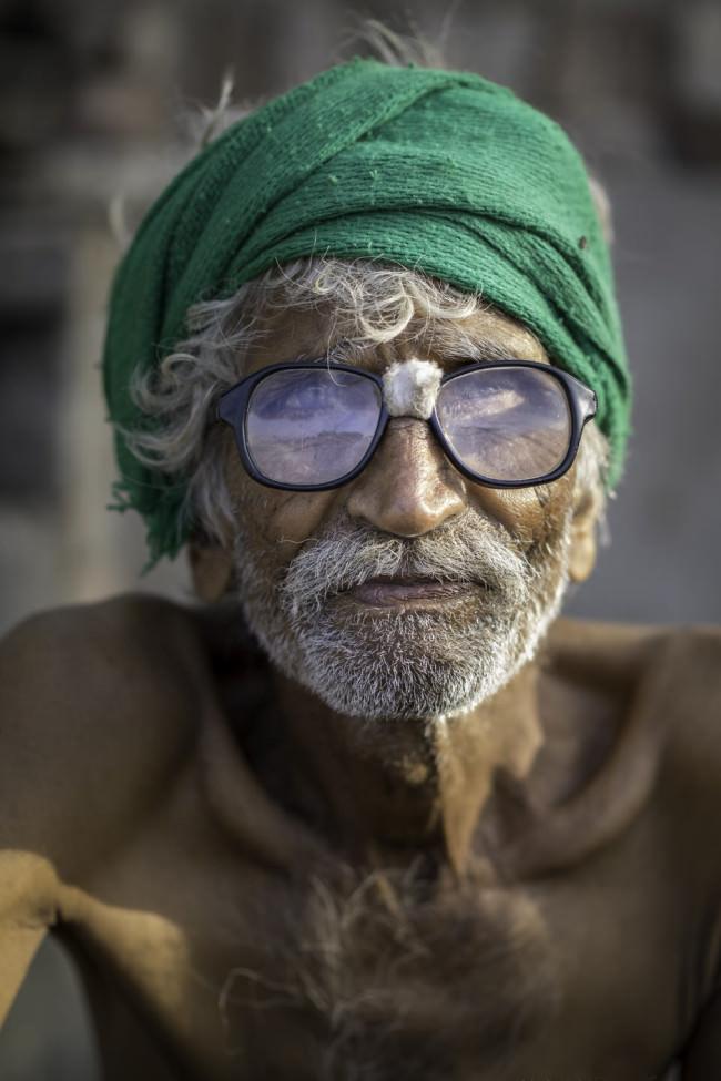 Ein Mann mit grünem Turban und starker Brille schaut in die Kamera.