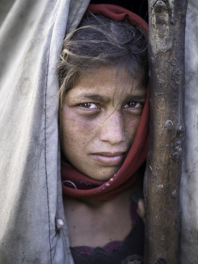 Ein Mädchen schaut aus einem Zelt heraus.