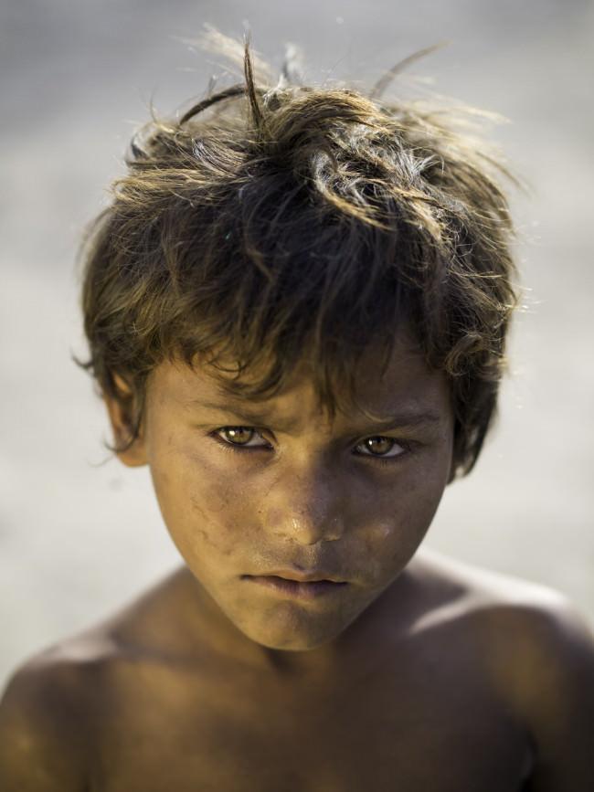 Ein Junge mit braunen Haaren und leuchtednen Augen schaut in die Kamera.