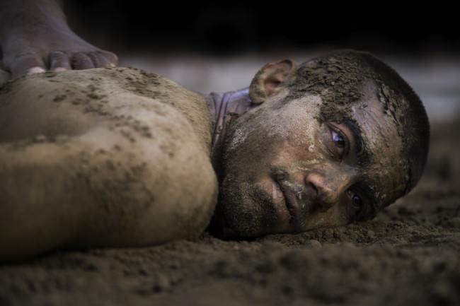 Ein Mann liegt ergeben auf dem Boden nach einem Kampf.